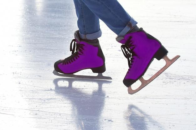 Pieds de personnes patinant sur une patinoire de rue. sports et vacances d'hiver