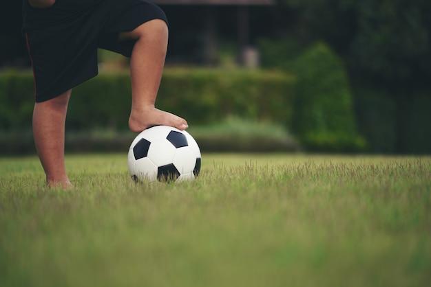 Pieds de petit garçon tenant le football au champ d'herbe