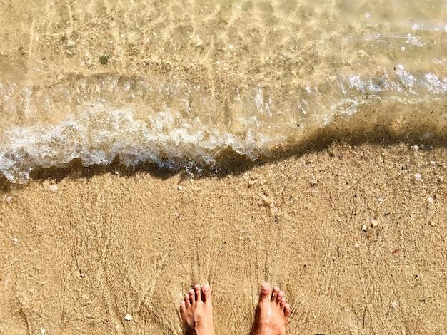 Pieds sur la plage de sable et vague douce