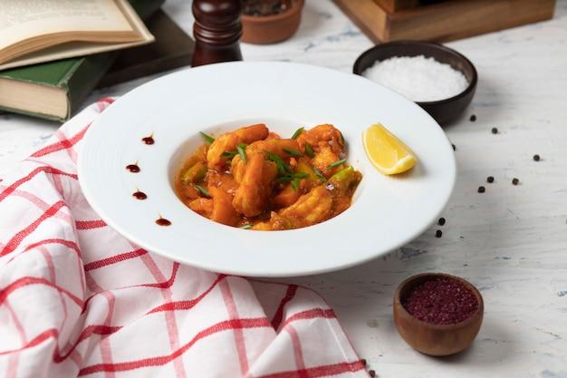 Pieds de poulet à la sauce tomate dans un bol blanc avec des légumes et du citron.