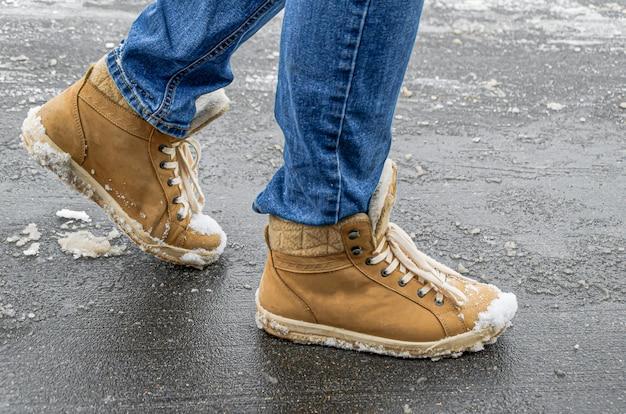 Pieds pour femmes en jean et bottes demi-saison en daim sur asphalte avec neige et réactifs. utilisation de réactifs pour nettoyer les rues de la ville de la neige, des dommages aux chaussures en daim et en cuir.