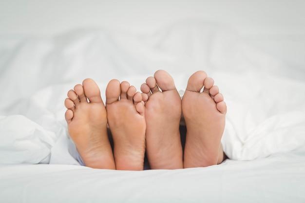 Les pieds qui sortent de la couverture dans la chambre