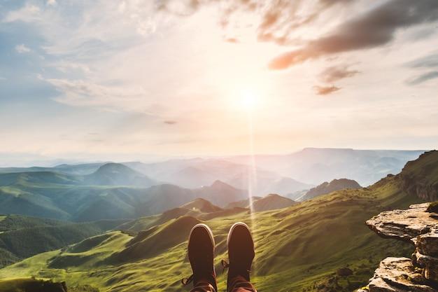 Pieds selfie hipster chaussures voyageur relaxant sur les montagnes de la falaise en plein air avec coucher de soleil aérien vue du soir sur les montagnes en arrière-plan style de vie randonnée concept de voyage vacances d'été