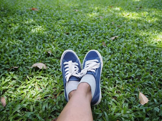 Pieds de selfie portant des baskets bleues sur l'herbe verte dans le parc.