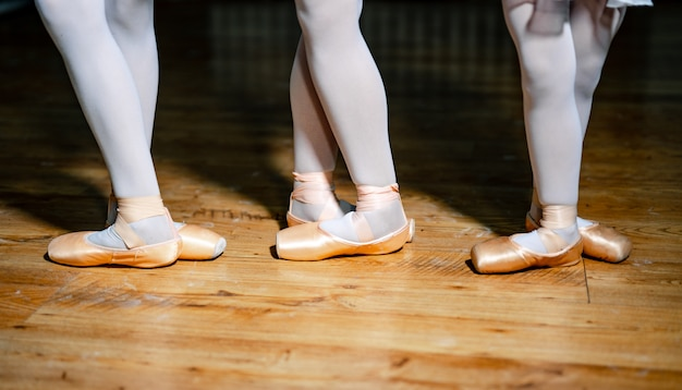 Pieds de trois jeunes ballerines en chaussons de pointe