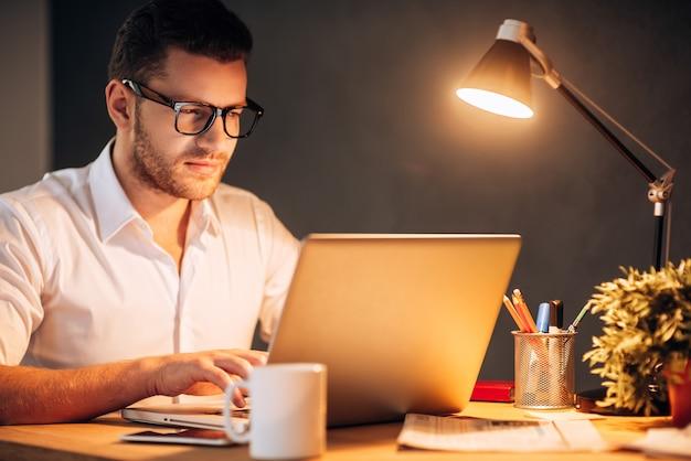 Piégé au bureau. jeune homme confiant en lunettes travaillant sur son ordinateur portable