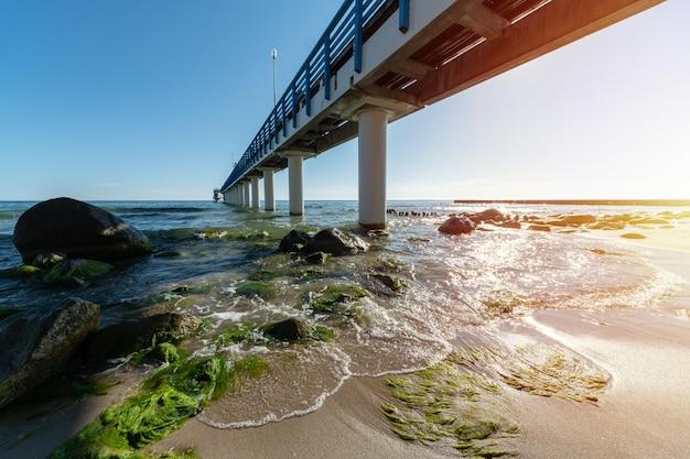 Pier sur la côte. vagues de surf avec écume de mer et algues sur une plage touristique. belle côte au soleil. paysage marin de jour.