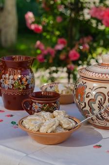 Pierogi fait maison dans des plats ukrainiens ethniques d'argile sur une table dans le jardin d'été.