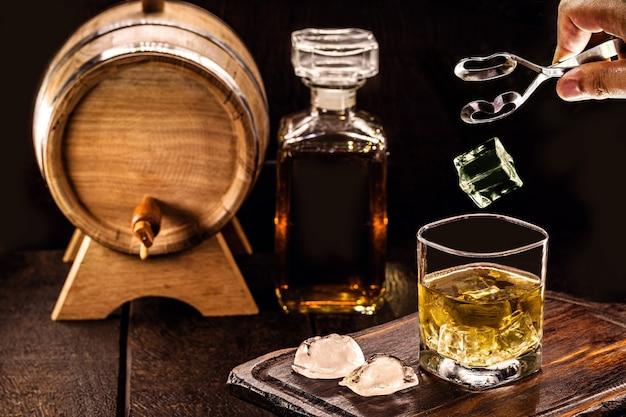 Pierre de glace tombant dans un verre à whisky âgé, espace pour le texte, toile de fond de pub