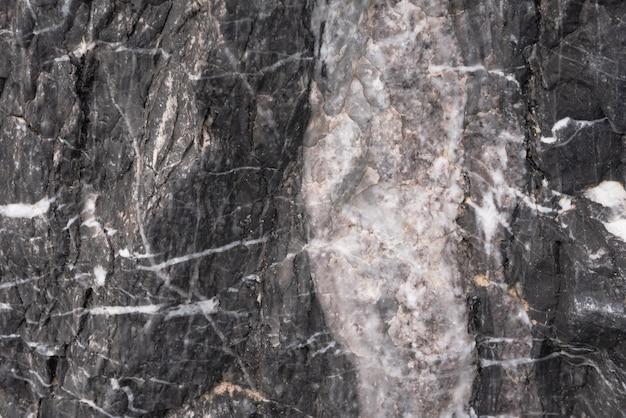 Pierre noire avec des rayures blanches et du sable