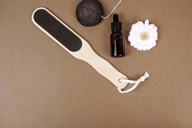 Pierre ponce naturelle pour exfolier la peau sur fond marron à côté de la fleur et sérum hydratant
