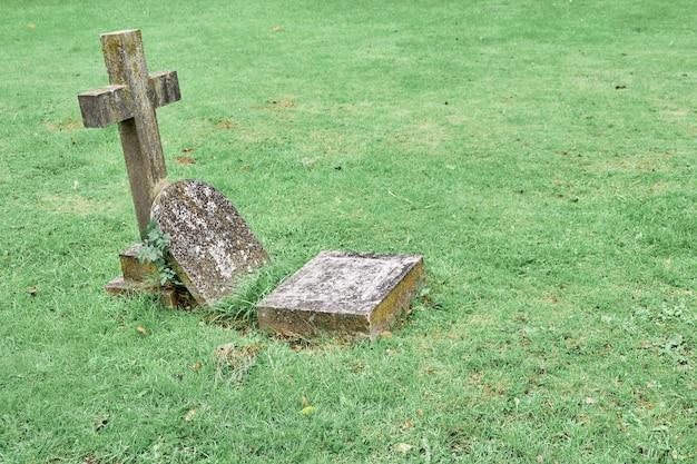 Pierre tombale patinée isolée sur un vieux cimetière.