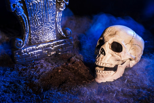 Pierre tombale près du crâne au sol