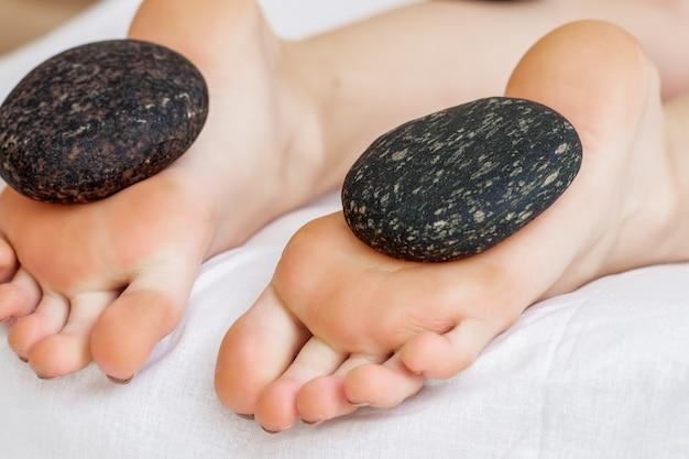 Pierres chaudes allongées sur des pieds féminins
