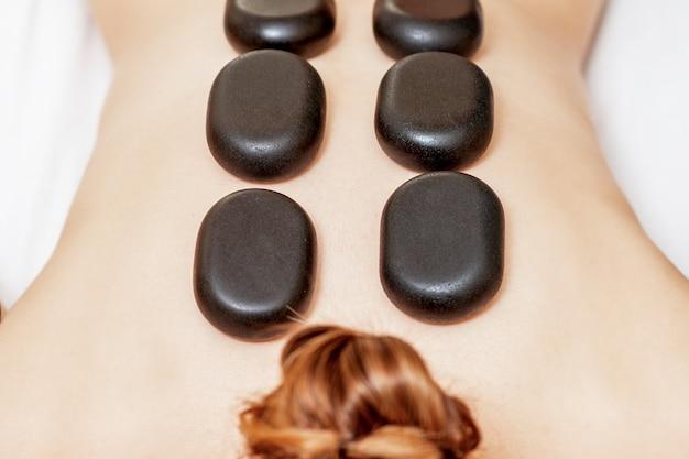 Pierres chaudes noires allongées sur le dos des femmes