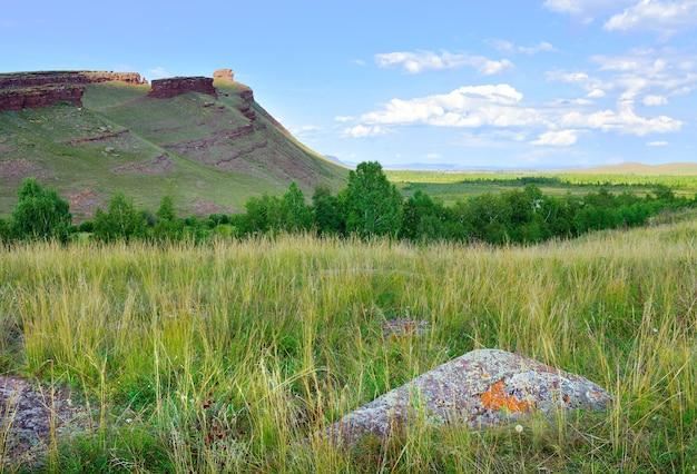 Pierres sur la colline avec des falaises de roche rouge en été sous un ciel bleu. sibérie, russie