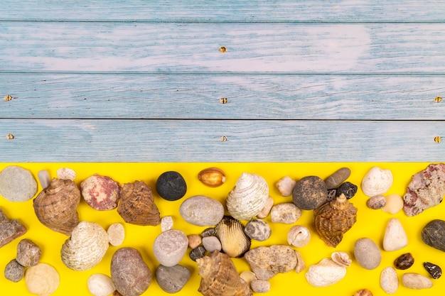 Pierres et coquillages sur fond bleu en bois et fond jaune. thème marin