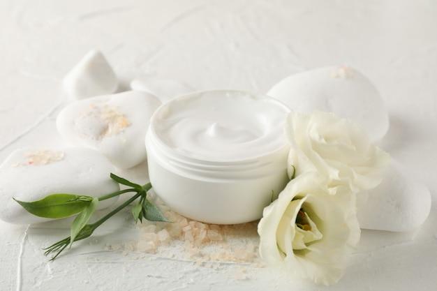 Pierres, crème, sel et fleurs sur fond blanc, close up
