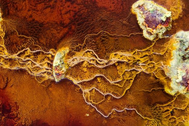 Pierres dans les eaux rouges reliées par des stromatolites jaunes
