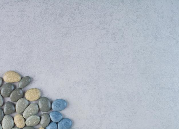 Pierres décoratives colorées pour l'artisanat sur fond de béton.