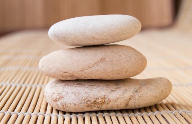 Pierres empilées dans une pyramide pour la méditation, fond de tapis en bambou