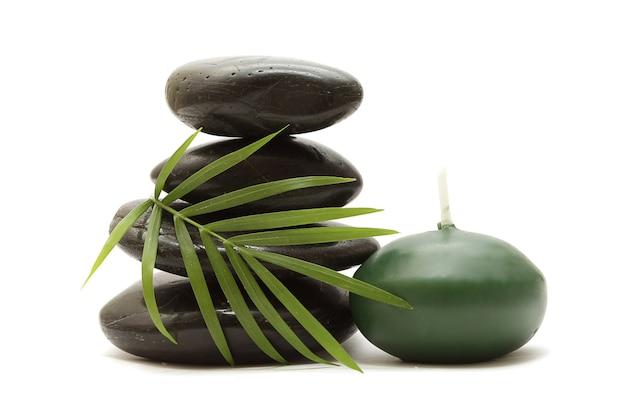 Des pierres, des feuilles vertes et une bougie sur fond blanc