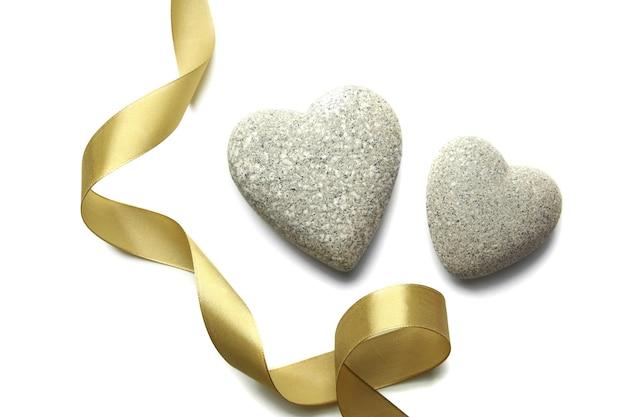 Pierres grises en forme de coeur et ruban de couleur, isolé sur blanc