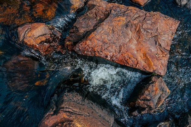 Pierres lisses en gros plan d'eau de source. l'eau propre s'écoule entre les pierres rouges et oranges.