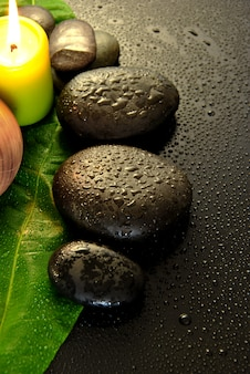 Pierres de massage humides avec feuille verte et gouttes d'eau