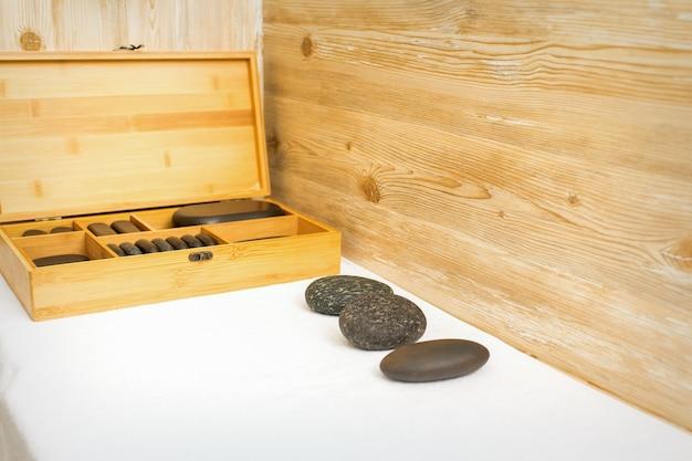 Pierres De Massage Noires Se Trouvant Près De La Boîte En Bois Avec Des Pierres De Massage Sur La Serviette Sur La Table. Photo Premium