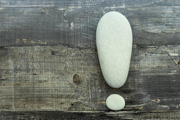 Les pierres de mer grises sont pliées en forme de point d'exclamation sur une surface en bois.