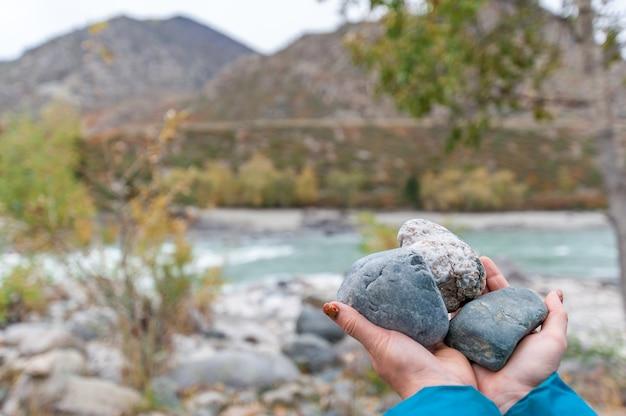 Pierres multicolores mains sur la rivière