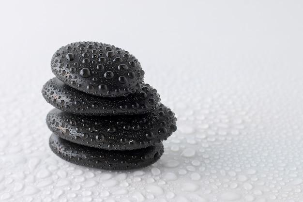 Pierres noires empilées sur fond blanc