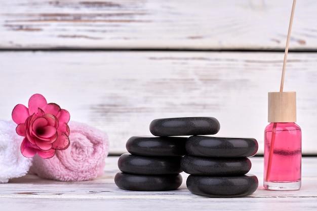 Pierres noires nature morte avec serviettes roulées et huile pour le corps