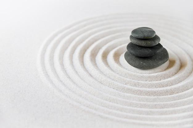 Des pierres noires s'entassent dans le sable. surface de jardin japonais zen