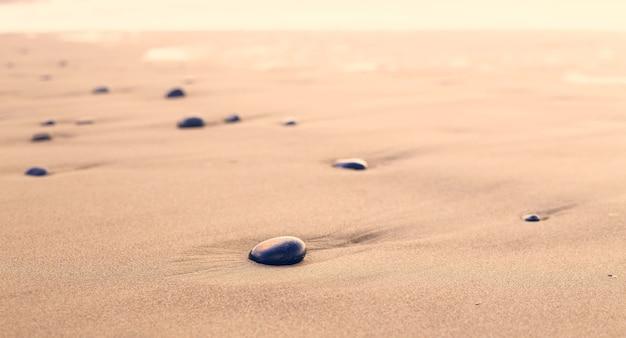 Pierres noires sur le sable du désert