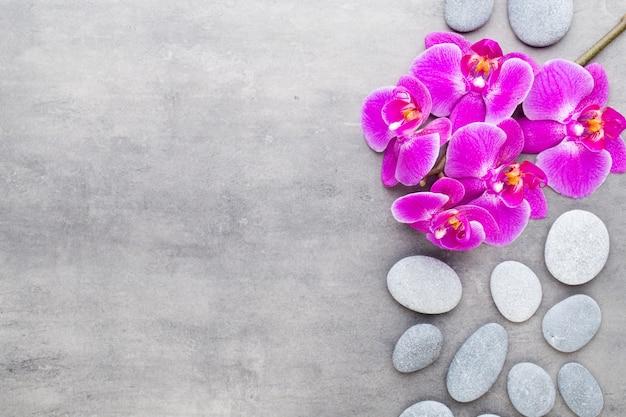 Pierres d'orchidée et spa sur fond de pierre. spa et scène wellnes.