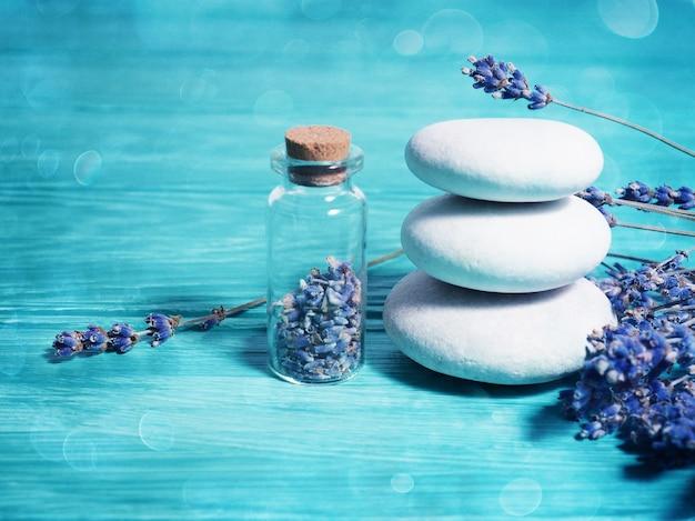 Pierres de pile zen sur fond bleu en bois, graines de lavande dans une bouteille et branches de lavande à proximité.