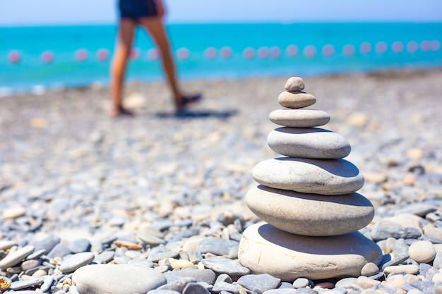 Des pierres plates rondes sont empilées en pyramide sur une plage de galets. au fond la mer et les jambes des touristes à pied.