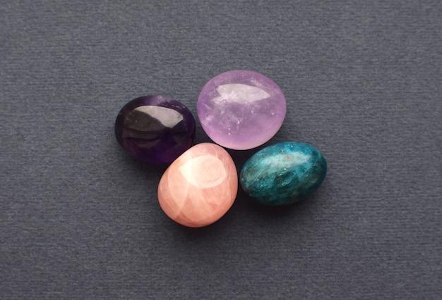 Pierres précieuses multicolores, pierres tumbling taillées. améthyste, quartz rose, apatite sur un mur gris.