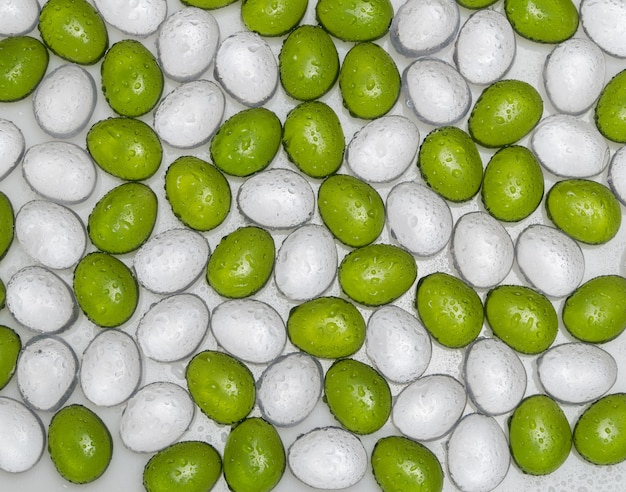 Pierres rondes artificielles avec goutte d'eau de couleur verte et blanche, vue de dessus. cailloux d'imitation