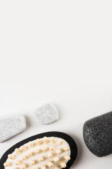 Pierres de spa; brosse de massage et pierre ponce sur fond blanc