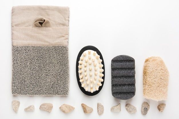Pierres de spa disposées en rangée avec du luffa; brosse de massage; les laveurs; pierre ponce sur fond blanc