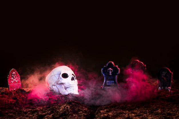 Pierres tombales et crâne entre le brouillard rose sur le sol