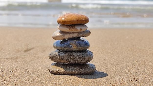 Pierres zen disposées à la main allongé sur le sable de la plage de la mer