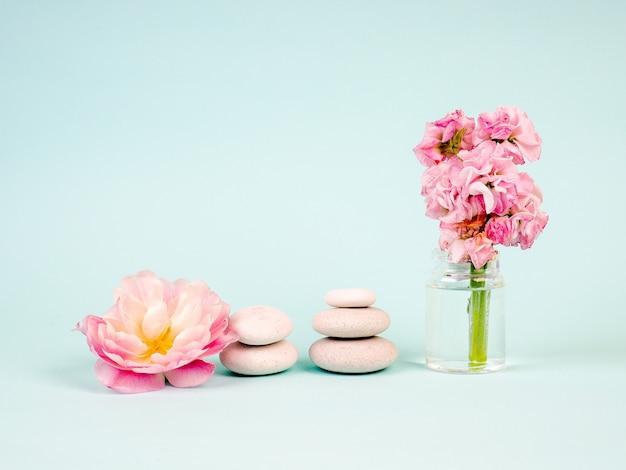 Pierres zen et fleurs roses sur fond bleu.