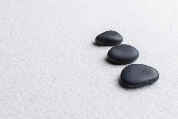 Pierres zen noires empilées sur fond blanc dans le concept de bien-être