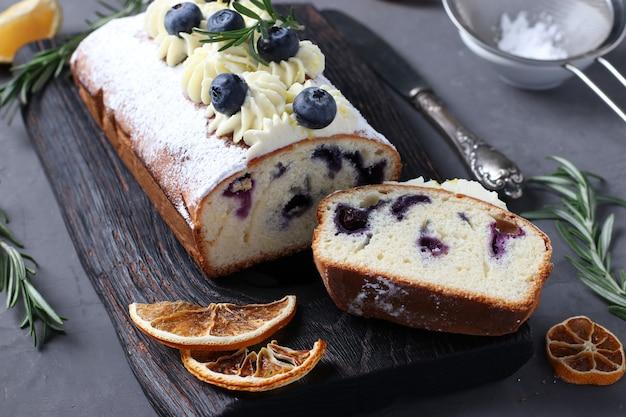 Piese gâteau maison avec crème de biscuit décorée de citron et de myrtille.