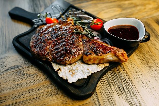 Pieu avec les tomates, l'oignon et la sauce sur la plaque de bois.