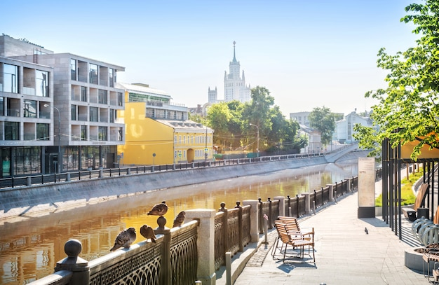 Les pigeons sur la clôture du canal vodootvodny à moscou et un gratte-ciel sur le quai de kotelnicheskaya au loin par une matinée ensoleillée. légende: remblai ovchinnikovskaya